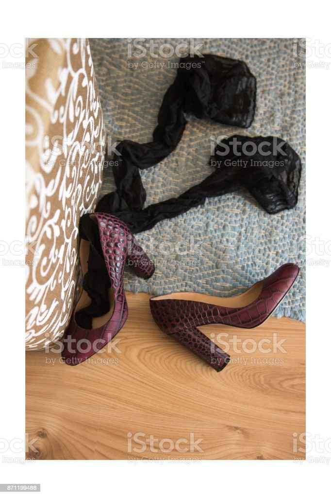 Female silk stockings and elegant shoes thrown to the floor stock photo