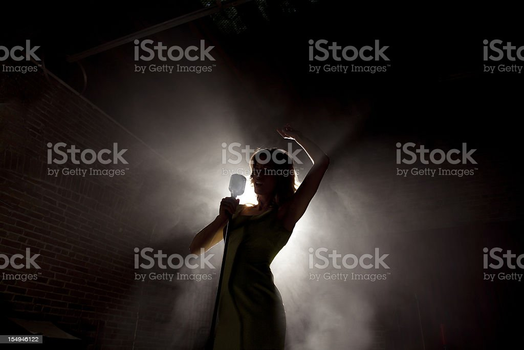 Female singer backlit on a smokey stage stock photo