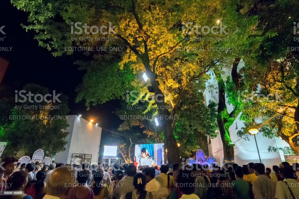 A female singer performing and seen in big screen amongst audience. stock photo