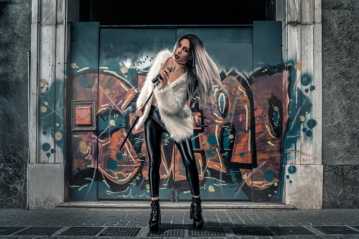 Female singer performing on the street on urban background with graffiti