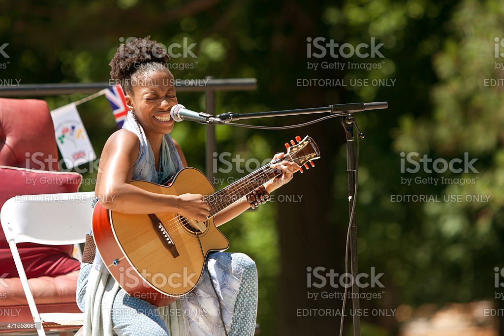 Female Singer Plays Guitar And Sings At Festival royalty-free stock photo