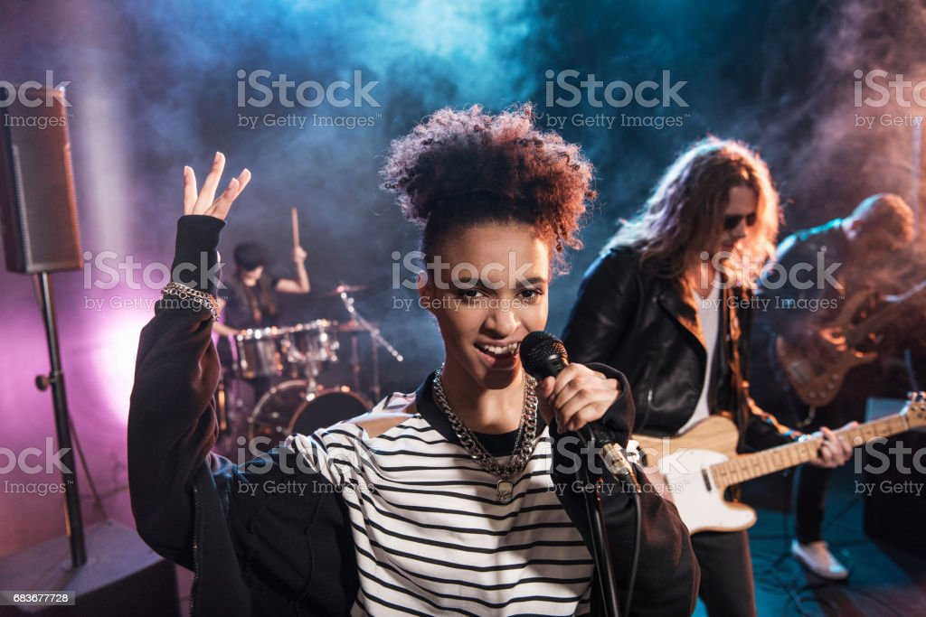 Female Singer With Microphone And Rock And Roll Band Performing Hard Rock Music On Stage Stock Photo Download Image Now Istock