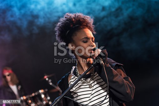 istock Female singer with microphone and rock and roll band performing hard rock music on stage 683677778