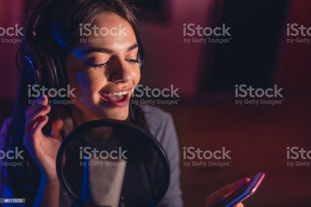 Female singing a sing with mobile phone at recording studio stock photo