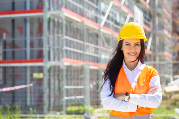 Female site supervisor wearing safety vest and helmet stands confidently in front of the construction covered in scaffolding. stock photo