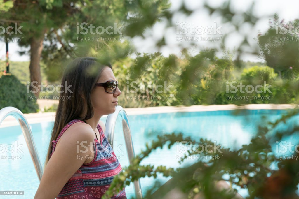 Female Sits Near By Swimming Pool at Summer Time Phone Bozcaada in Canakkale Turkey 2017 stock photo