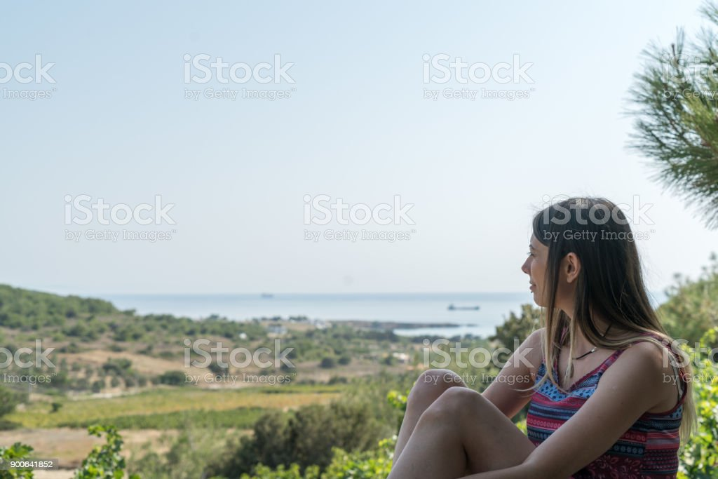 Female Sits Near By Valley at Summer Time Phone Bozcaada Canakkale Turkey 2017 stock photo