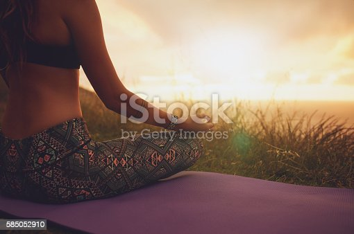 Close up shot of female sitting in lotus yoga pose on exercise mat, with focus on hands. Fitness female meditating outdoors during sunset.