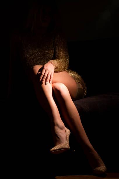 frauen sitzen auf dem bett, mit einem bein gekreuzt über das andere, im dunklen raum mit niedrigen lampe beleuchtet - glitzer absätze stock-fotos und bilder