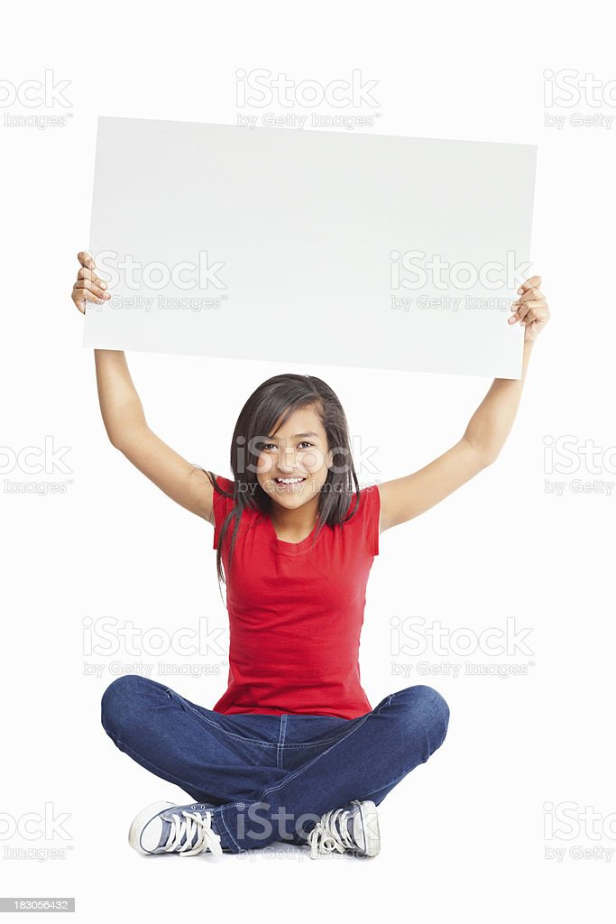 Female sitting on floor as she holds up a billboard royalty-free stock photo