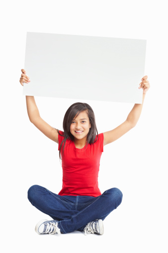 Portrait of a happy female child sitting on floor as she holds up a billboard to display your text