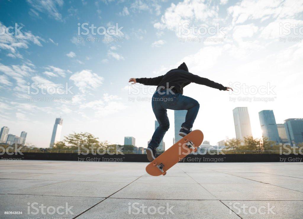 female skateboarder jumping on city with skateboard – zdjęcie
