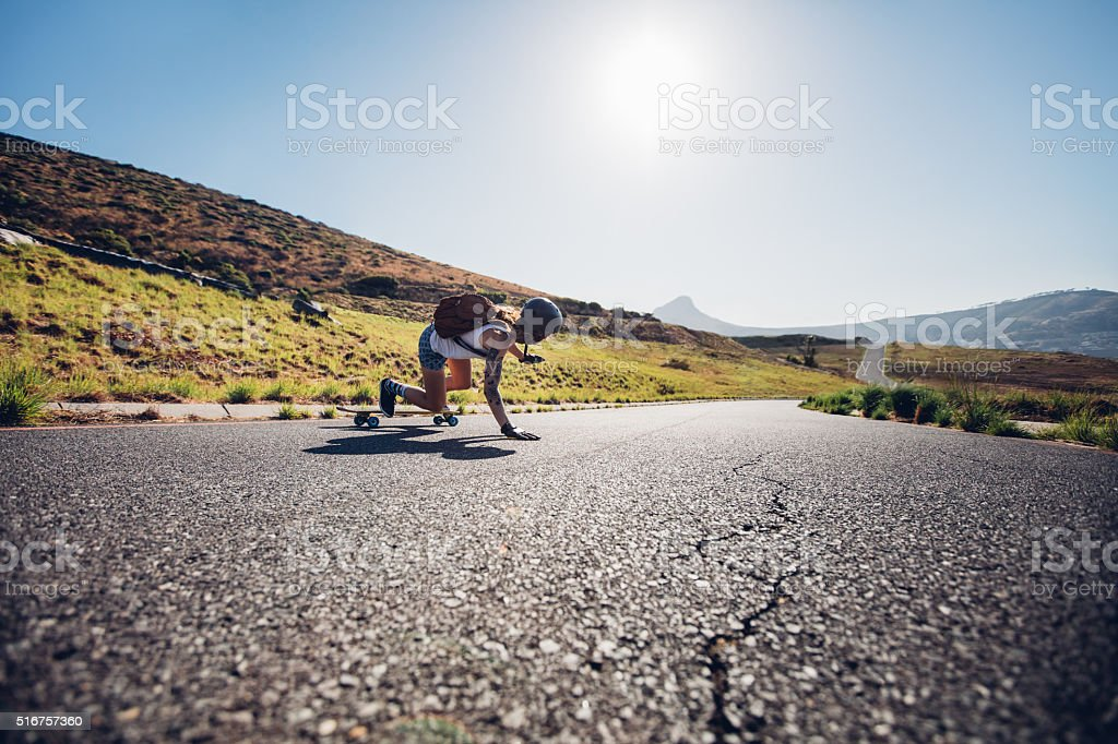 Female skater practicing skateboarding on rural roads stock photo