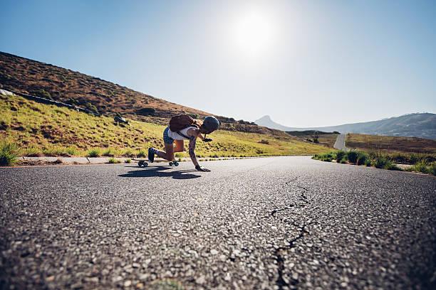 Female skater practicing skateboarding on rural roads stock photo