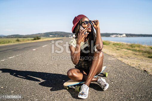Smiling female skater sitting on skateboard on road and using smart phone.
