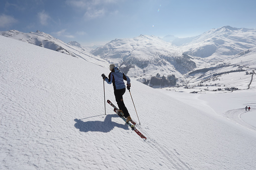 Female ski mountaineer ascends mountain slope.