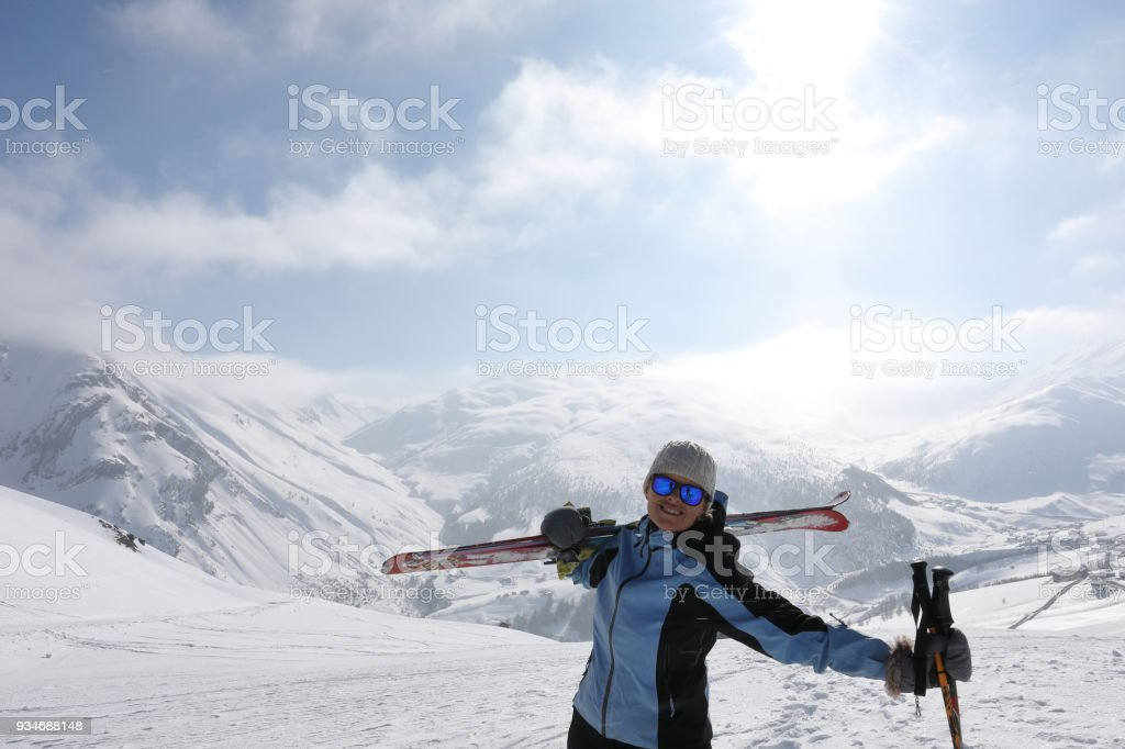 Female ski mountaineer pauses to look out to mountains stock photo