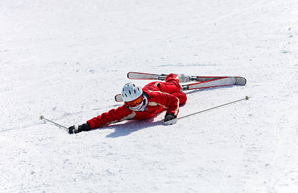 Female skier after falling down on a mountain slope stock photo