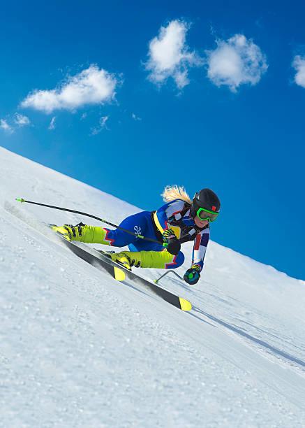 weibliche skifahrer in der straße bergab rennen - skirennen stock-fotos und bilder