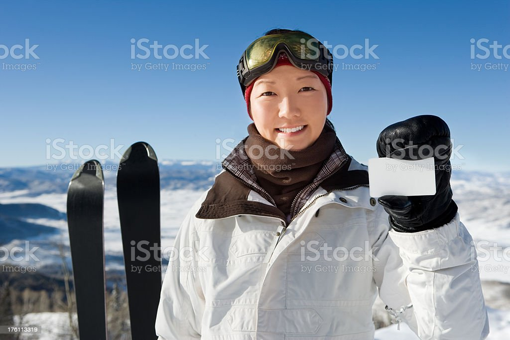 female skier holding credit card. stock photo