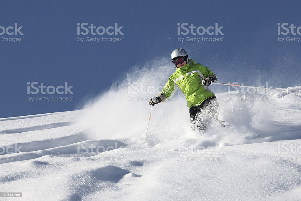 Female skier in green under blue skies stock photo