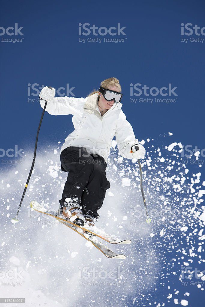 Female Skier Jumping Against A Blue Sky royalty-free stock photo