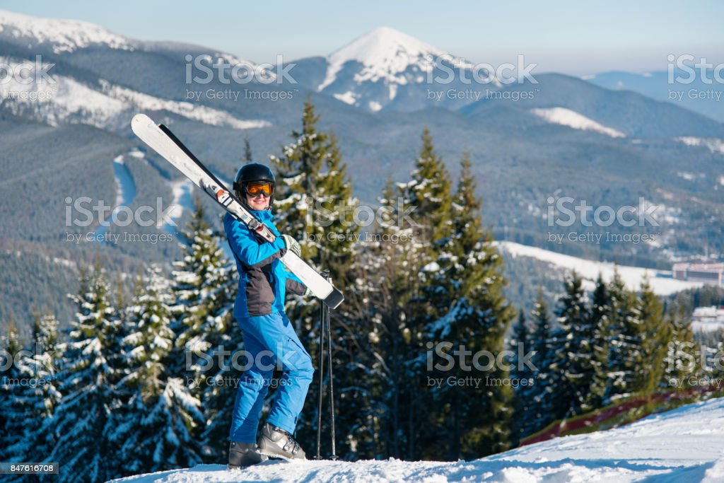 513e77e35fd Female skier standing on top of a hill wearing blue ski suit mask and black  helmet