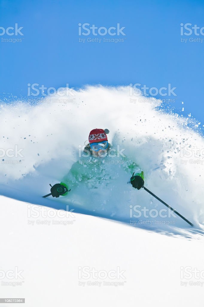 Female skiing in deep powder stock photo