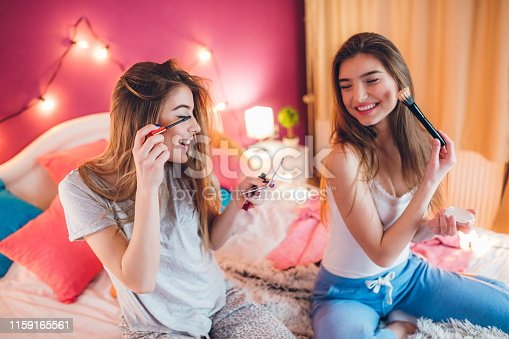 Two beautiful teenage girls having a pijamas party. Putting make-up on in fun.