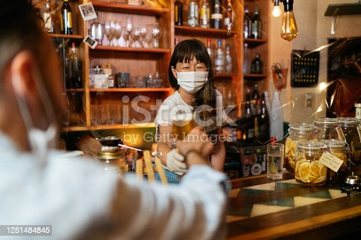 A female small bar owner is giving beer to customer from behind a protective clear plastic curtain.