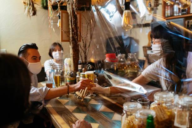 女小酒吧老闆從保護透明塑膠窗簾後面給顧客啤酒 - 吧 公共飲食地方 個照片及圖片檔