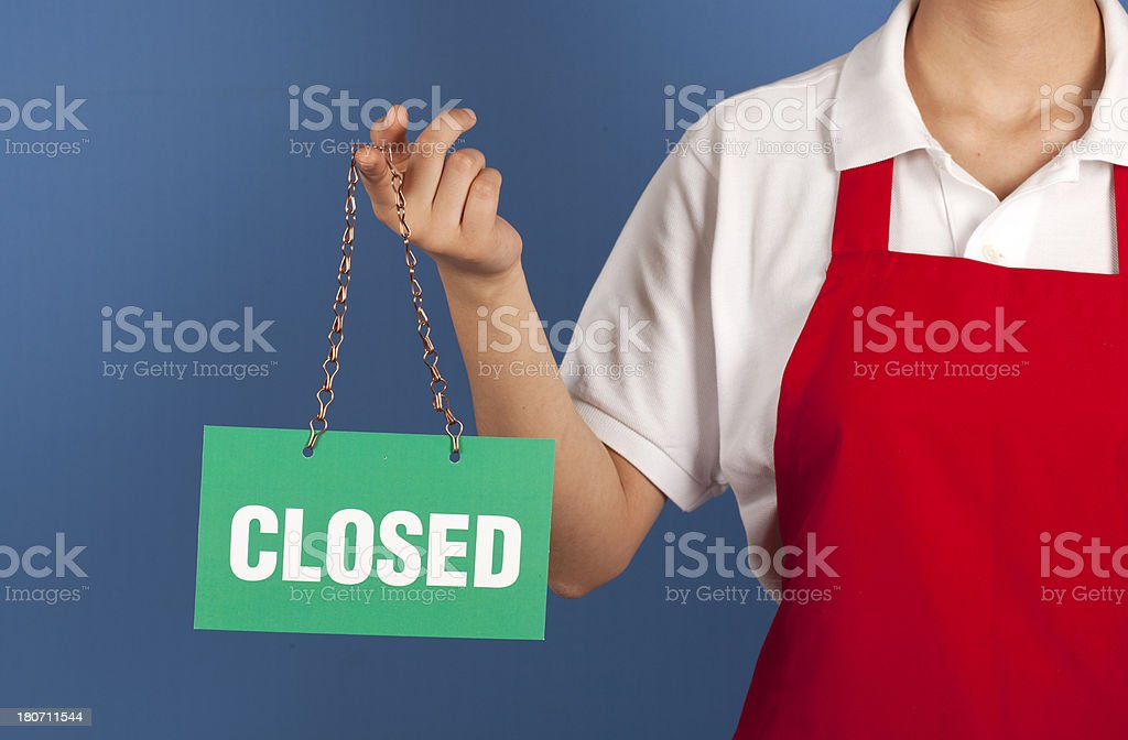 Female small business owner holding up CLOSED sign