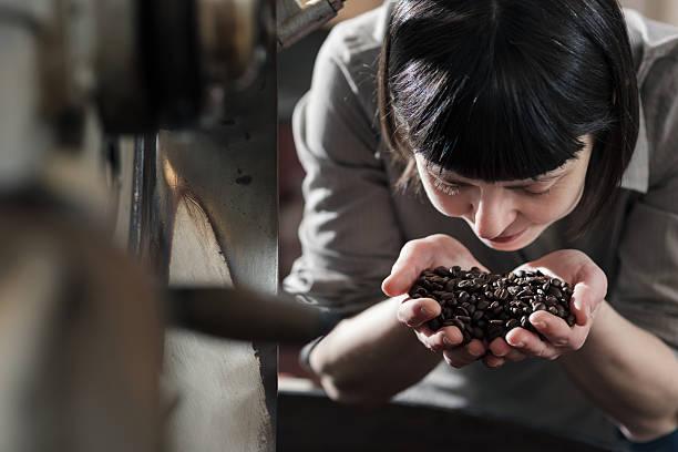 Weibliche Kleinunternehmen Eigentümer riechen frisch gerösteten Kaffee – Foto