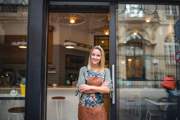 Female Small Business Owner Standing at Open Door stock photo