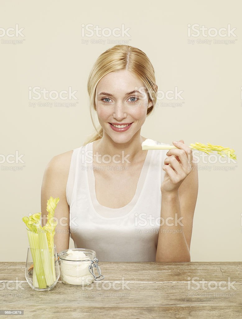 female smiling about to eat celery and humus royalty-free stock photo