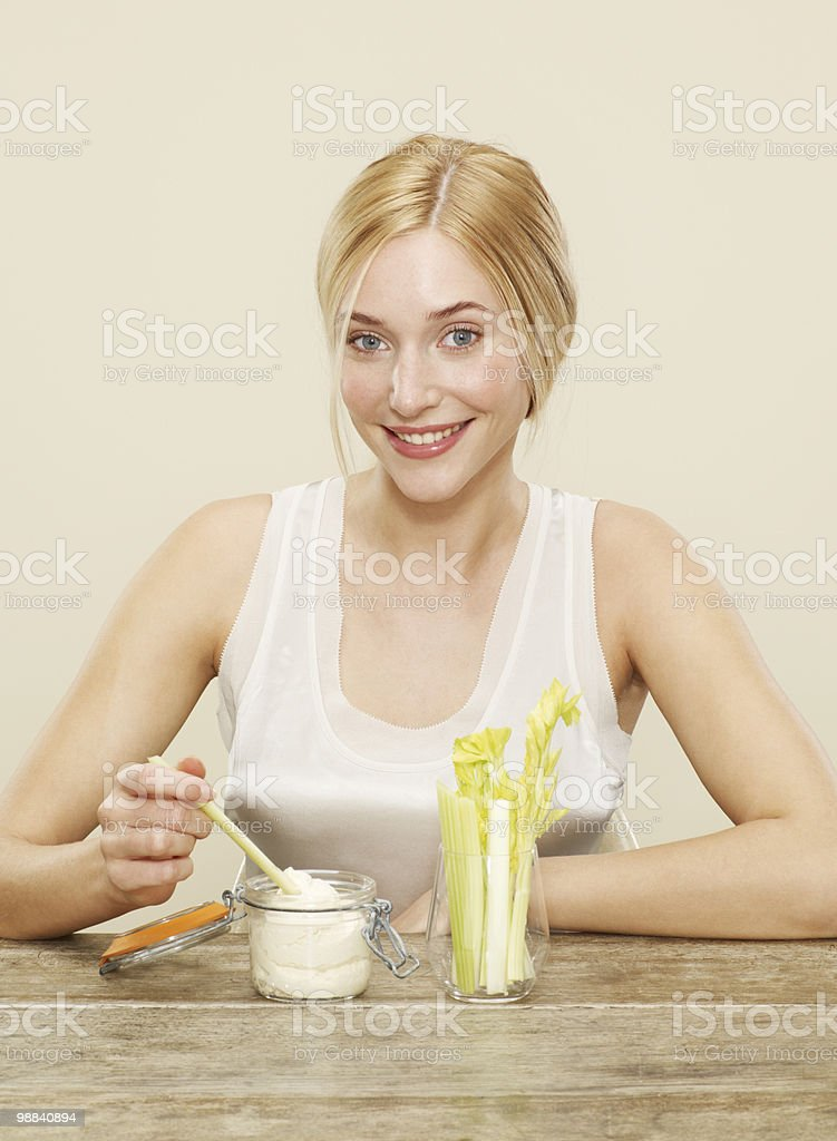female smiling as she dips celery into humous royalty-free stock photo