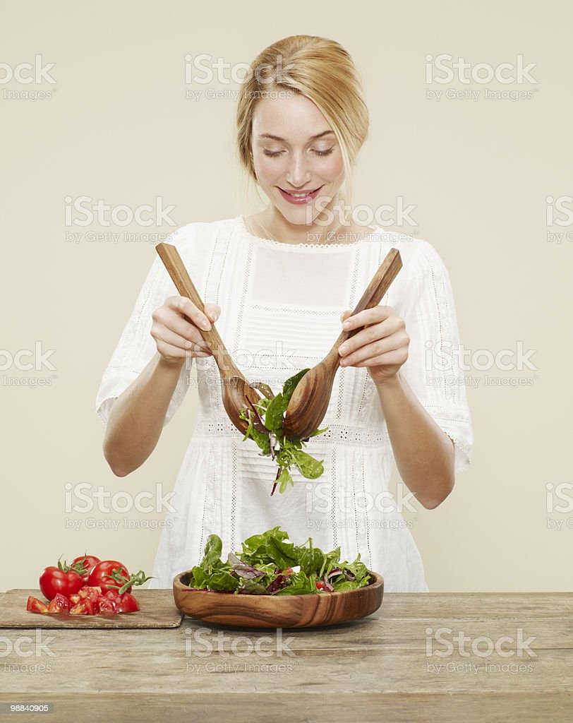 female smiling as she tosses a fresh salad royalty-free stock photo
