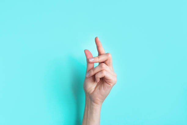Female snapping hand Female snapping hand on blue background, copy space. Fingers snapping. Snap gesture, minimal concept. snapping stock pictures, royalty-free photos & images