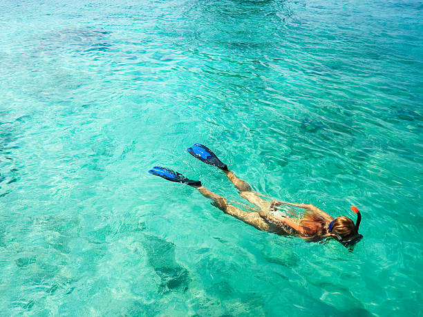 A female snorkeling in the blue water