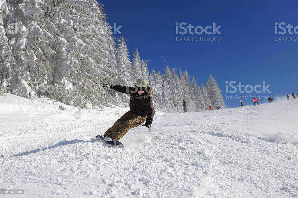 Female Snowboarder carving on the Slopes stock photo
