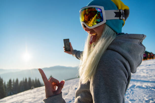 Female snowboarder enjoying sunset after snowboarding, using her smart phone, taking pictures of winter nature in the mountains copyspace connectivity mobility freeride lifestyle concept Female snowboarder enjoying sunset after snowboarding, using her smart phone, taking pictures of winter nature in the mountains copyspace connectivity mobility freeride lifestyle concept ski goggles stock pictures, royalty-free photos & images