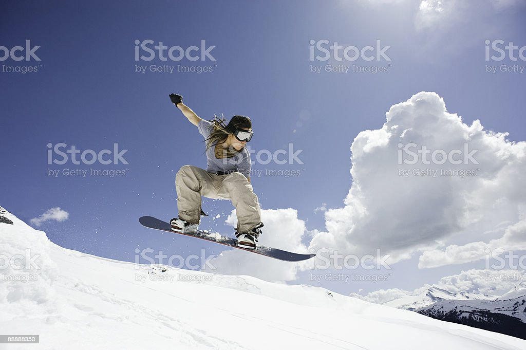 female snowboarder jumping through air royalty-free stock photo