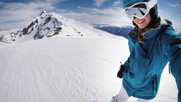 Female snowboarder selfie Young woman snowboarding and taking selfie taken on mobile device stock pictures, royalty-free photos & images