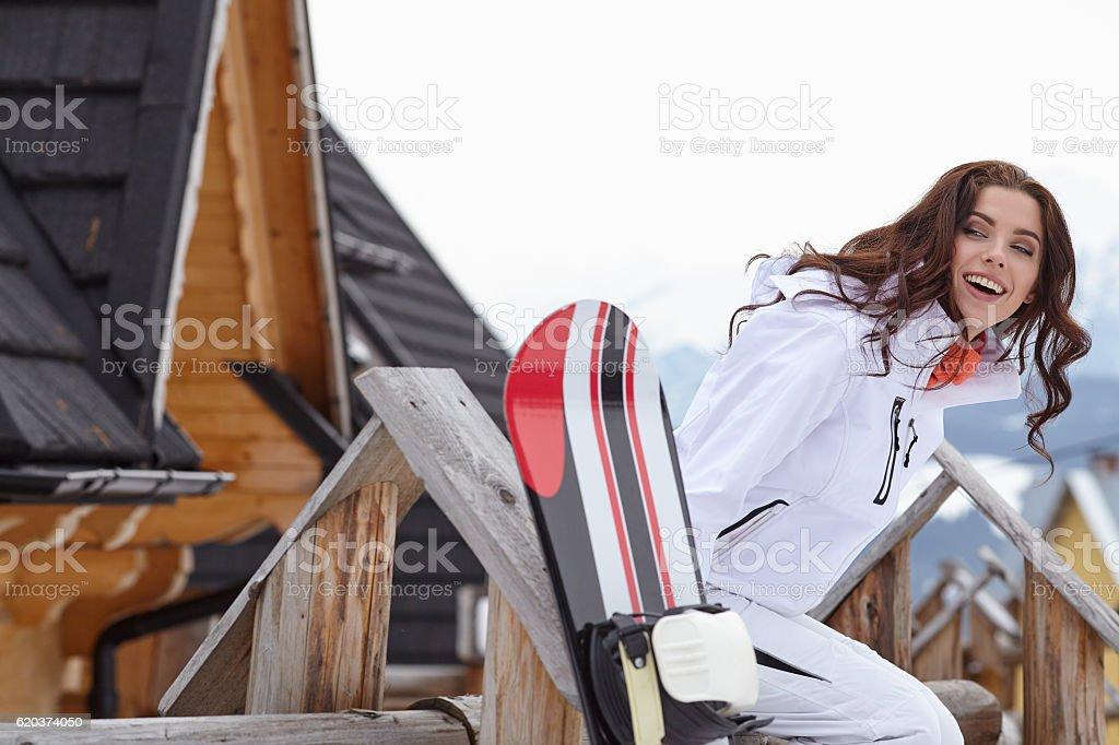 Female snowboarder standing with snowboard in resort zbiór zdjęć royalty-free