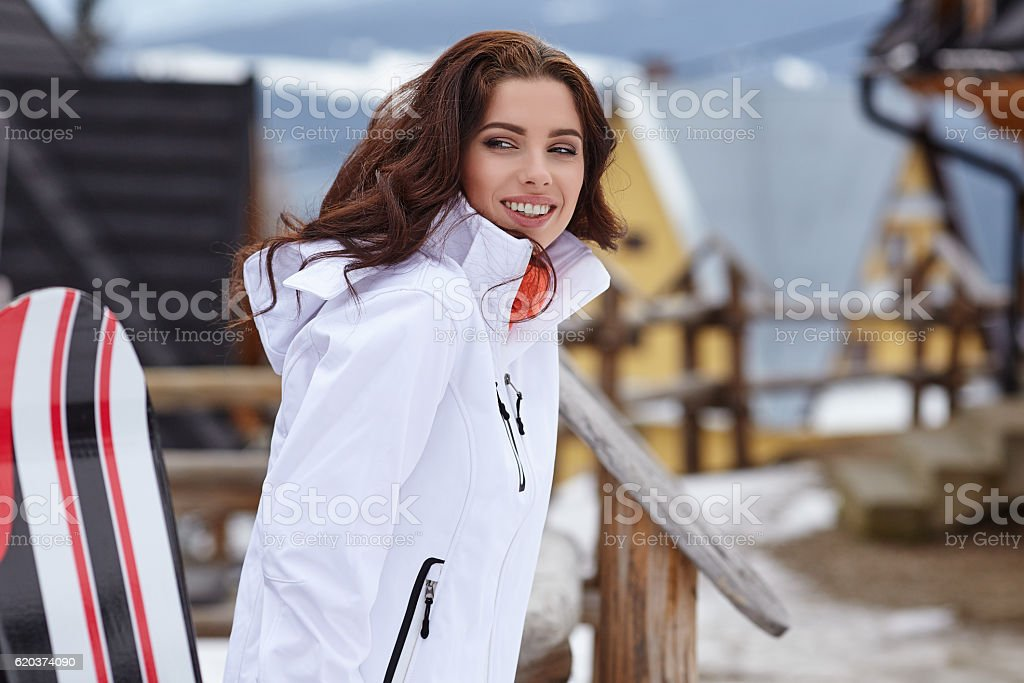 Female snowboarder standing with snowboard in resort foto de stock royalty-free