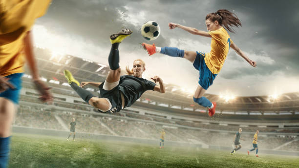 Female soccer or football players kicking ball at the stadium stock photo
