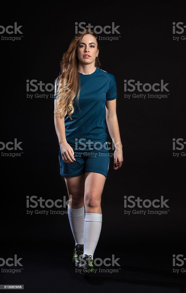 female soccer player go ahead isolated on black background stock photo