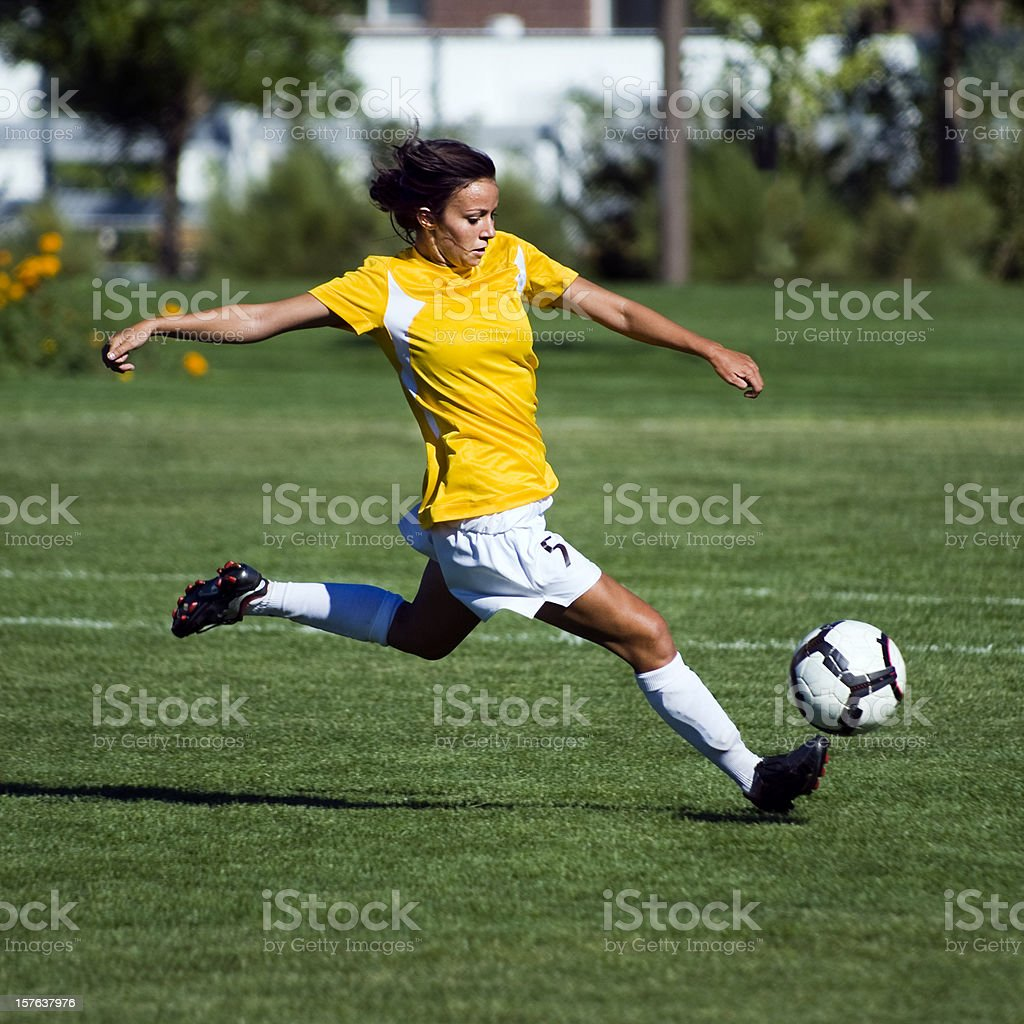 Female Soccer Player in Yellow Jumps to Touch Bouncing Ball royalty-free stock photo