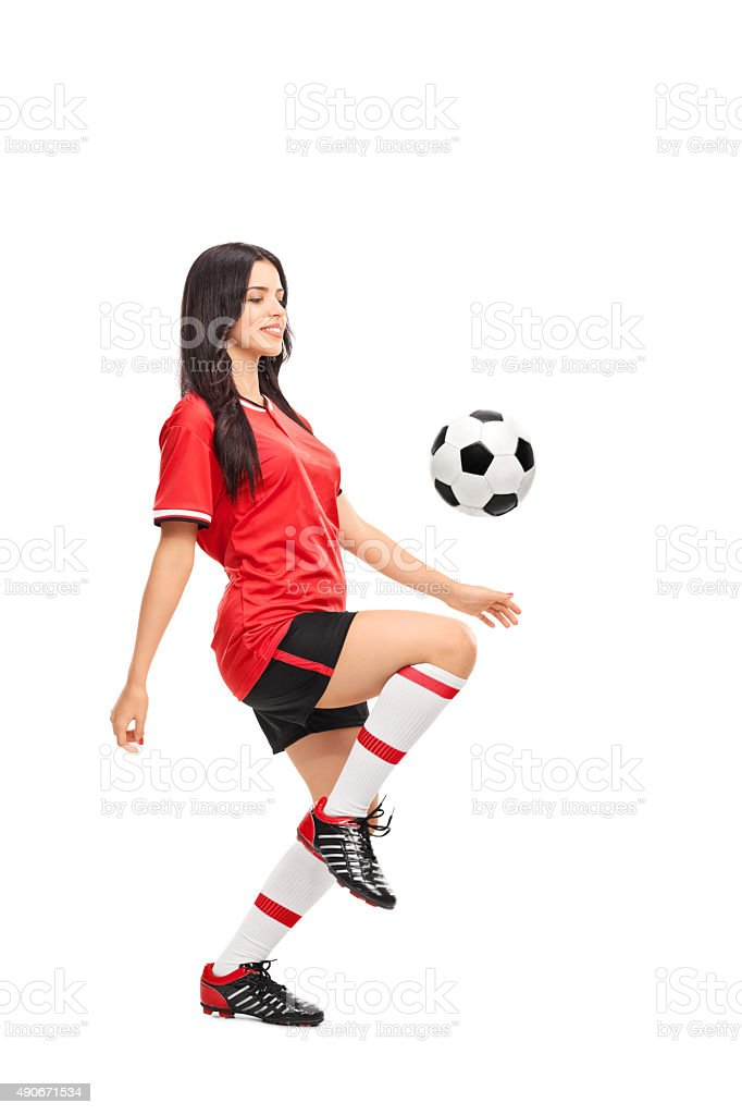 Female soccer player juggling a ball stock photo