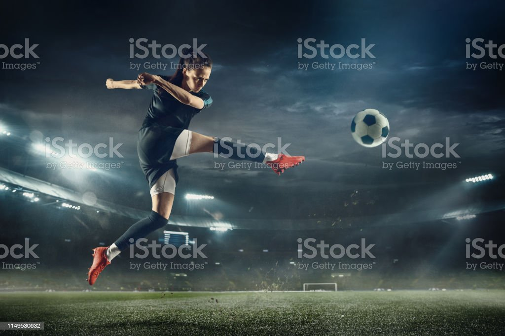 Vrouwelijke voetbalspeler schoppen bal in het stadion - Royalty-free Alleen volwassenen Stockfoto